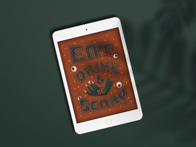 "ipad laying on a dark green background, featuring custom artwork that says ""eat, drink, and be scary"" with eyeballs and a zombie hand"